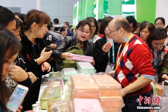 11月10日,首届中国国际进口博览会食品及农产品展区,参观者扫码支付购买商品。中新社记者 殷立勤 摄