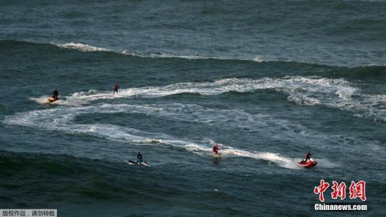资料图片:人们在海中乘风破浪。