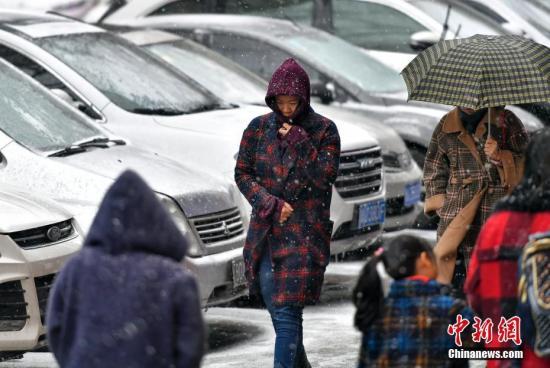 11月12日,持续浓雾天气的新疆乌鲁木齐市,又迎来一场雨雪天气,气温随之骤降。据新疆气象台预报,13日到15日,新疆大部分地区将出现降温和雨雪天气,相比于降水,降温更加明显。届时,北疆大部降温达8至10摄氏度,南疆地区普遍降温5至8摄氏度。图为风雪中,民众裹紧衣领脚步匆匆。中新社记者 刘新 摄