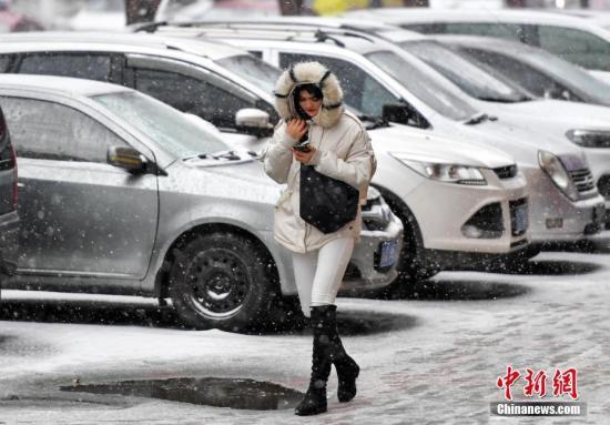 11月12日,持续浓雾天气的新疆乌鲁木齐市,又迎来一场雨雪天气,气温随之骤降。据新疆气象台预报,13日到15日,新疆大部分地区将出现降温和雨雪天气,相比于降水,降温更加明显。届时,北疆大部降温达8至10摄氏度,南疆地区普遍降温5至8摄氏度。图为风雪中,民众裹紧衣领脚步匆匆。 <a target='_blank' href='http://www-chinanews-com.qfnmb.com/'>中新社</a>记者 刘新 摄