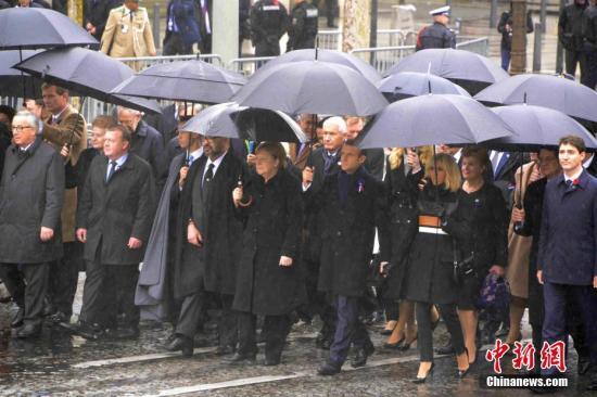 当地时间11月11日,纪念一战结束100周年官方仪式在巴黎凯旋门隆重举行。图为法国总统马克龙、德国总理默克尔、加拿大总理特鲁多、欧盟委员会主席容克等政要在雨中共同走向凯旋门的仪式现场。中新社记者 李洋 摄