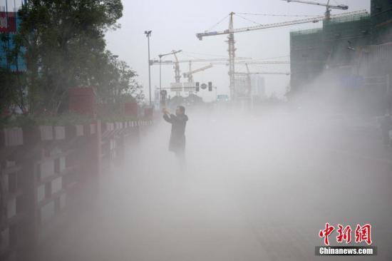 11月13日下午,成都市成华区街头开启了喷雾除霾装置抵御雾霾,市民置身其中若隐若幻。 张浪 摄