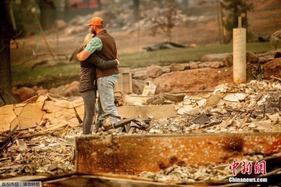 """资料图:一对男女站在被""""坎普""""山火焚烧成废墟的家上相拥。"""