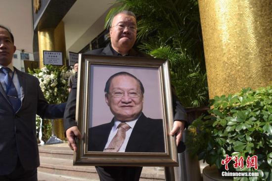 11月13日,香港作家金庸私人丧礼于香港殡仪馆举行。早上11时,金庸灵柩移出殡仪馆,儿子查传倜提着父亲照片送别亲友。 中新社记者 李志华 摄