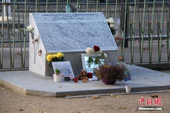 2018年11月13日是巴黎恐怖袭击三周年。图为巴黎巴塔克兰剧场附近为逝者设立的纪念碑。因为当天巴塔克兰剧场周边区域被封锁,悼念者无法靠近纪念碑,因而纪念碑前只摆放了少量花束等纪念物。2015年11月13日的巴黎恐怖袭击造成130人遇难,其中有90人是在巴塔克兰剧场被害的。中新社记者 李洋 摄