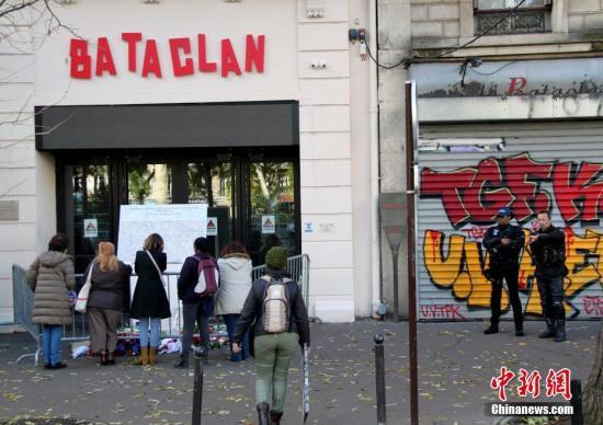 2018年11月13日是巴黎恐怖袭击三周年,民众在恐袭事发地之一巴黎巴塔克兰剧场悼念,警察站在一旁警戒。2015年11月13日的巴黎恐怖袭击造成130人遇难,其中有90人是在巴塔克兰剧场被害的。中新社记者 李洋 摄