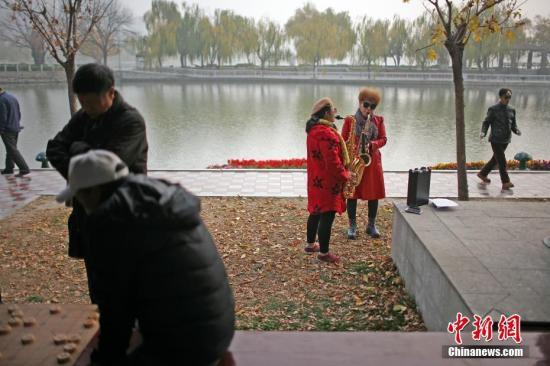 11月14日,天津空气遭遇重度污染。两位市民在公园中吹萨克斯。<a target='_blank' href='http://www-chinanews-com.cszkd.com/'>中新社</a>记者 佟郁 摄