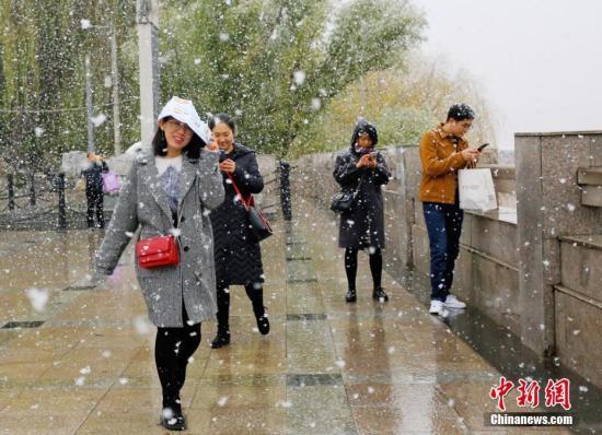 11月14日,甘肃省兰州迎来降雪,顶风冒雪的市民在路边拍照、玩雪。高展 摄