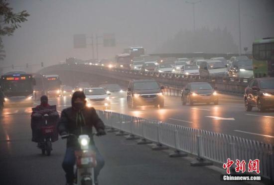 11月14日,市民在重污染天气出行。 中新社记者 贾天勇 摄