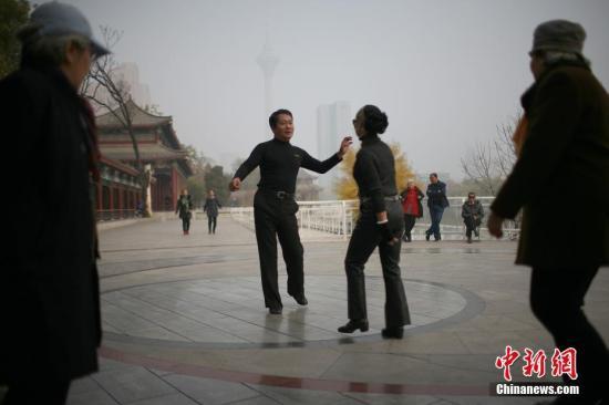 11月14日,天津空气遭遇重度污染。图为市民在公园中跳舞。 中新社记者 佟郁 摄