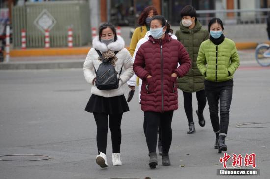 11月14日,呼和浩特市街头,民众戴口罩出行。当日,内蒙古自治区多地出现空气污染。中新社记者 刘文华 摄