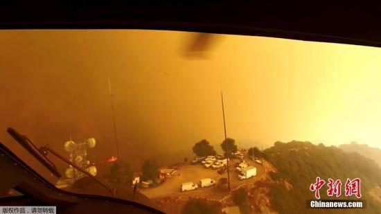 近日,在加州伍尔西山火火灾期间,救援人员动用直升机进行救援工作,飞行员所使用的头盔相机记录下了现场画面。图为直升机飞行员在寻找着陆点。