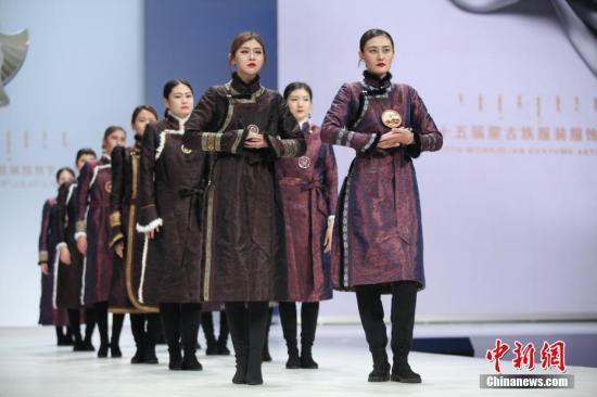 """11月20日,蒙古族休闲情侣生活装进行""""T台秀""""展示。当日,""""第十五届蒙古族服装服饰艺术节""""总决赛休闲装比赛正在内蒙古呼和浩特市如火如荼地进行,这个走过14年历程的经典赛事活动,逐步让来自""""远古""""的28个蒙古族部落文化之美走出草原,走向国际。中新社记者 郭伟伟 摄"""