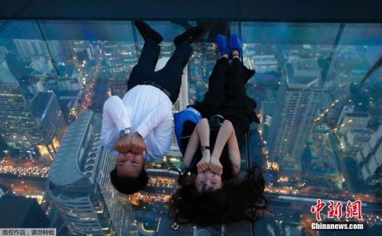 当地时间11月21日,泰国曼谷地标建筑王权云顶大厦(King Power MahaNakhon)的全新空中玻璃步道对外开放,游客在玻璃步道上体验空中漫步的刺激。