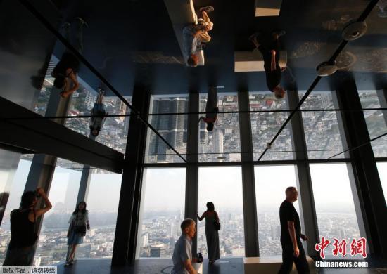 当地时间11月21日,泰国曼谷地标建筑王权云顶大厦(King Power MahaNakhon)的全新空中玻璃步道对外开放,游客在玻璃步道上体验空中漫步的刺激。曼谷王权云顶大厦有314米高,共78层,是泰国第一高楼。登上王权云顶大厦,可以360度俯览曼谷全景。