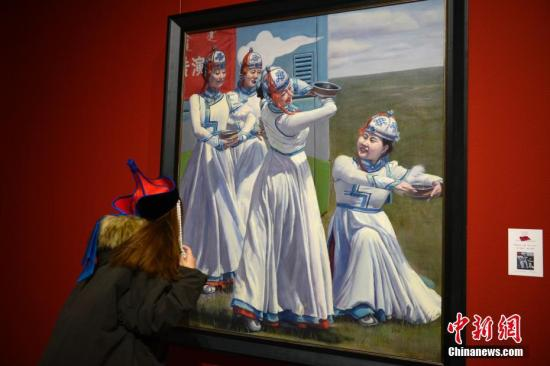 """11月23日,观众欣赏油画作品《草原上的白云》。近日,""""弘扬乌兰牧骑精神--内蒙古乌兰牧骑主题美术作品展览""""在位于呼和浩特市的内蒙古美术馆开幕。记者 刘文华 摄"""