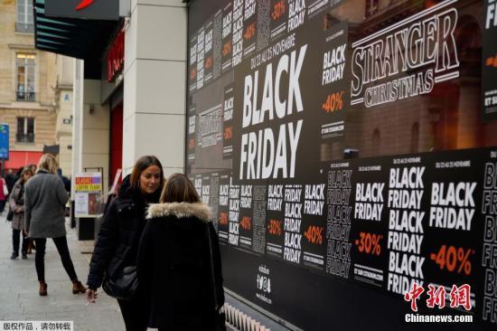資料圖:法國巴黎民眾經過貼滿打折廣告的街頭。