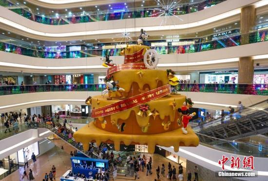11月24日,距离圣诞节还有一个月时间,香港许多大型购物广场开启圣诞购物季的大幕,纷纷装点商场,搭建圣诞装置,营造节日气氛,以招揽更多顾客光临。图为铜锣湾时代广场将迪士尼米老鼠90周年庆典引入今年的圣诞购物季,以巨大的蛋糕装置装点商场。<a target='_blank' href='http://www-chinanews-com.aqxxsy.com/'>中新社</a>记者 张炜 摄