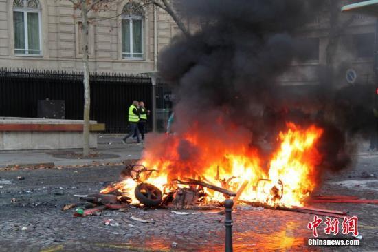 当地时间11月24日,巴黎香榭丽舍大街遭遇大规模示威活动。数以千计示威者聚集在街上,设置了不少路障,街道交通完全陷入瘫痪。图为示威者在香榭丽舍大街附近点燃的大火。<a target='_blank' href='http://www.chinanews.com/'>中新社</a>记者 李洋 摄