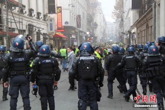 当地时间11月24日,巴黎香榭丽舍大街遭遇大规模示威活动。数以千计示威者聚集在街上,设置了不少路障,街道交通完全陷入瘫痪。图为法国警方当天在香榭丽舍大街附近与大批示威者对峙。/p中新社记者 李洋 摄