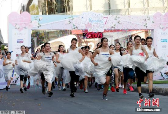 """资料图:泰国曼谷举办""""新娘快跑""""比赛活动,300名准新娘在准新郎的陪伴下参加3公里的赛跑活动。"""