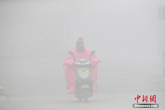 11月26日,全国多地出现大雾天气,影响市民出行。中央气象台26日晨通报,全国多地出现低能见度的大雾天气,江苏中南部、浙江北部、安徽南部等地能见度不足500米,局地能见度不足50米。图为安徽省淮北市民戴口罩在大雾中骑车出行。中新社发 谢正义 摄 图片来源:CNSPHOTO