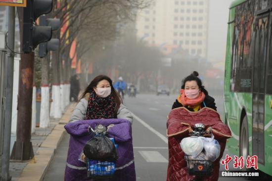 11月26日,呼和浩特市市民戴口罩出行。当日,内蒙古自治区中西部大范围出现浮尘天气,空气严重污染。<a target='_blank' href='http://www-chinanews-com.cxhulian.com/'>中新社</a>记者 刘文华 摄