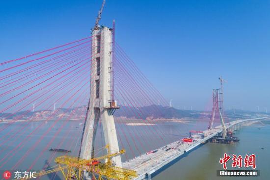 """11月28日,航拍位于江西九江市境内的都九高速公路鄱阳湖二桥。当日,中国最大淡水湖鄱阳湖上又一座跨湖大桥——鄱阳湖二桥正式相符龙。鄱阳湖二桥全长5589米,是江西在建里程最长、跨径最大的桥梁,也是现在中国国内高速公路跨内地湖泊最长的斜拉桥。当天相符龙的鄱阳湖二桥位于被称为""""中国百慕大""""的鄱阳湖老爷庙水域,建设难度在国内可谓稀奇。鄱阳湖常年怪风荼毒,飞絮扬沙,不见天日。时而狂风大作,时而暴雨倾盆。老爷庙水域厉酷的当然环境,曾令施工单位看而生畏。熊国涛 摄 图片来源:东方IC 版权作品 请勿转载"""
