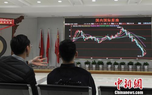 """11月19日,浙江舟山,两位市民在观看""""国内国际原油""""走势图。<a target='_blank' href='http://www-chinanews-com.tekanae.com/'>中新社</a>记者 张茵 摄"""