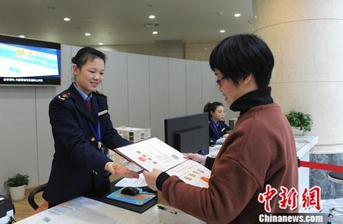 中国(浙江)自由贸易试验区,一位业主从工作人员手中接过办理好的营业执照。<a target='_blank' href='http://www-chinanews-com.tekanae.com/'>中新社</a>记者 张茵 摄