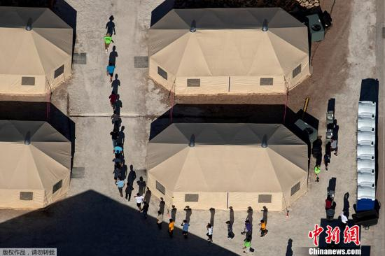 资料图:当地时间6月18日,美国德克萨斯州一所靠近墨西哥边境的拘留所里,与父母分离的移民儿童由工作人员带领排队穿行帐篷之间。MIKE BLAKE