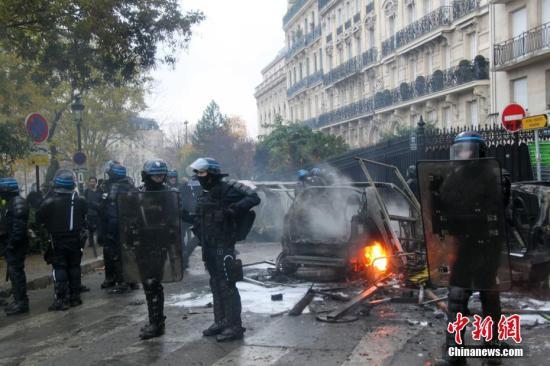 当地时间12月1日,巴黎再次发生大规模示威活动。示威者聚集在凯旋门。大批防暴警察寻求控制巴黎示威造成的混乱局面。图为防暴警察在巴黎市中心正在燃烧的车辆前严密警戒。 中新社记者 李洋 摄