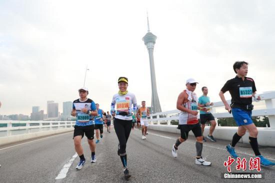 """资料图片:""""2018澳门银河娱乐国际马拉松""""在奥林匹克体育中心运动场起跑,图为选手经过著名景点旅游塔。中新社发 钟欣 摄"""