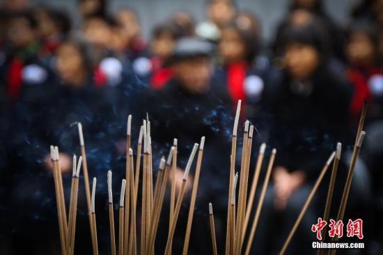 12月4日,在侵华日军南京大屠杀死难者名单墙前,南京大屠杀死难者遗属阮定东老人、李金城老人和他们的家人,通过献花、敬香和诵读家书等形式,祭奠亲人表达哀思。中新社记者 泱波 摄