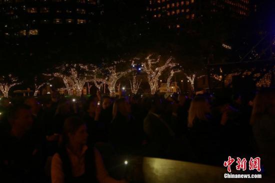 资料图:当地时间12月3日晚,在休斯敦市政厅前的赫曼广场上,当地民众举起手中的荧光棒,悼念美国前总统老布什逝世。<a target='_blank' href='http://www-chinanews-com.wenjunyz.com/'>中新社</a>记者 曾静宁 摄