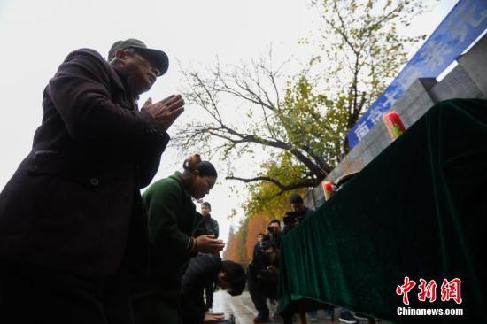 资料图:今年5月过世的南京大屠杀幸存者仇秀英的家人祭拜亲人。中新社记者 泱波 摄