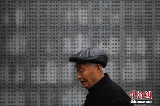 图为阮定东老人在刻有他爷爷名字的死难者名单墙前沉思。中新社记者 泱波 摄