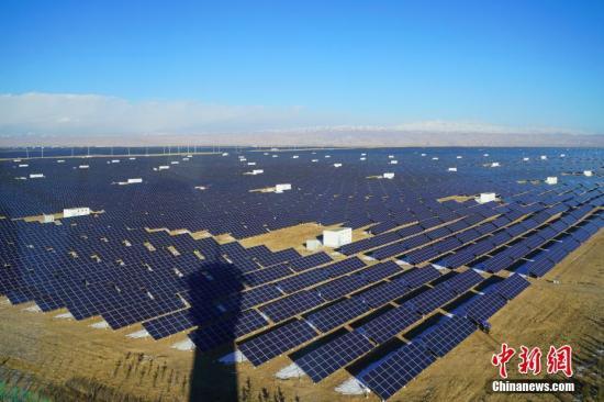 """12月1日,青海省海南藏族自治州共和县塔拉滩生态光伏发电园区内的太阳能光伏板。塔拉滩曾经是沙化严重的半荒漠化草地。近年来,随着青海省在海南共和大力推进光伏产业发展,塔拉滩依托其现有资源,着力推进生态光伏园区建设。如今,在塔拉滩的道路两旁,大面积的太阳能光伏板代替了光?#21644;?#30340;沙石地面,曾经的""""不毛之地""""变身太阳能生态发电园。<a target='_blank' href='http://www.chinanews.com/'>中新社</a>记者 张兴龙 摄"""