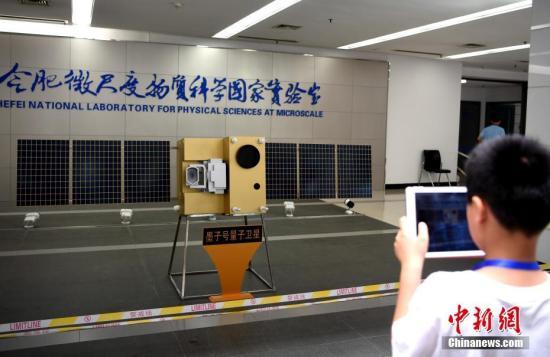 """2016年8月16日,中国成功发射世界首颗量子科学实验卫星""""墨子号""""。2017 年6月16日,中国""""墨子号""""量子卫星在世界上首次实现千公里量级的量子纠缠。图为一位小朋友正在拍摄""""墨子号""""模型。<a target='_blank' href='http://www.chinanews.com/'>中新社</a>记者 韩苏原 摄"""