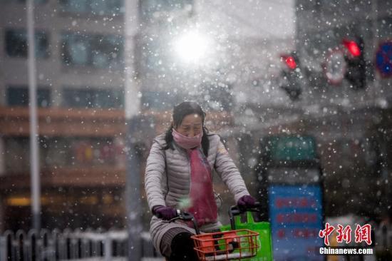 12月5日,山西省太原市迎入冬以来首场降雪,气温骤降,民众冒雪出行。 韦亮 摄