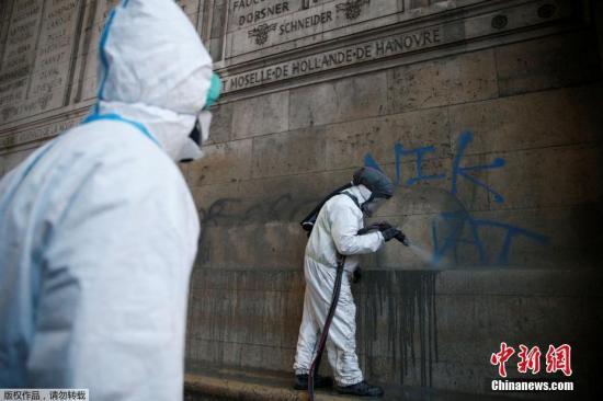 资料图:法国工作人员在修复被抗议者涂在凯旋门外墙上的涂鸦。