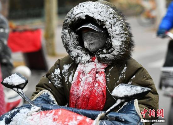 """资料图:一位市民的衣帽被雪""""覆盖""""。 中新社记者 翟羽佳 摄"""
