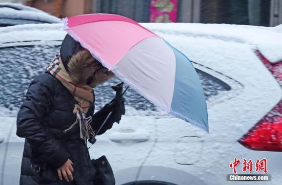 原料图:市民大风中出走。 中新社发 刘德斌 摄 图片来源:CNSPHOTO