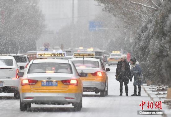 资料图:民众在路边等候出租车。中新社记者 刘新 摄
