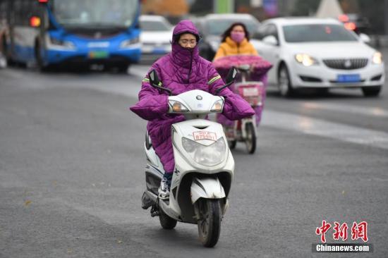 原料图:降温中民多骑电行车。 张浪 摄