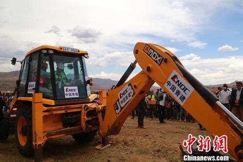 12月6日,中国援莱索托莫比蒂――塞赫拉巴泽贝道路升级优惠贷款项目在喀查斯内克(Qacha's Nek)正式开工。图为莱索托王国首相莫措阿哈・托马斯・塔巴内在开工仪式上驾驶挖土机为工程铲出第一方土。<a target='_blank' href='http://www.chinanews.com/'>中新社</a>记者 王曦 摄