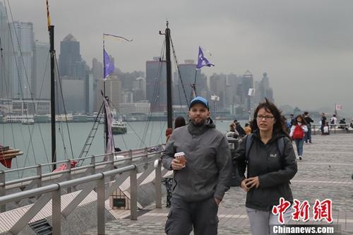 12月7日,在香港尖沙咀,不少外国游客穿上棉衣御寒。香港当日天气显著转凉,并伴随有阵雨。根据香港天文台预测,气温将在当天逐步下降,多区气温晚上将陆续下跌至只有17、18度。<a target='_blank' href='http://www-chinanews-com.zhaoweiya.com/'>中新社</a>记者 谢光磊 摄