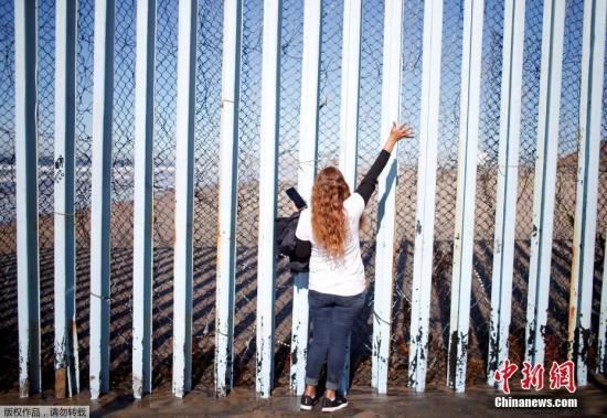 材料图:一位朱西哥男子站正在好朱疆域墙朱西哥一侧,背好国圣天逊徵一侧的家人挨号召。