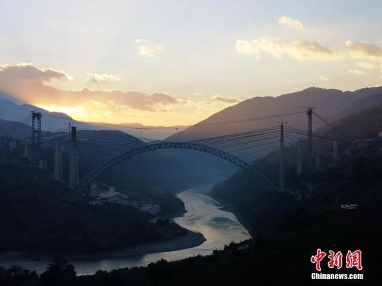12月10日,大(理)瑞(丽)铁路全长1024米的怒江四线特大桥实现钢桁拱合龙,该桥是目前世界上跨度最大的铁路拱桥。中新社发 张伟明 摄