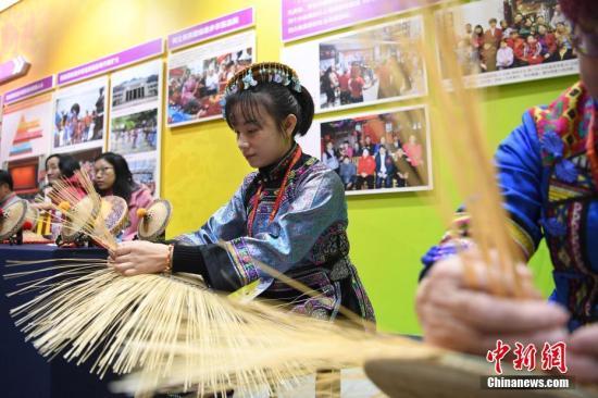12月10日,别名壮乡青年正在系统毛南族花竹帽。当天,广西壮族自治区60周年收获展在南宁开展。中新社记者 侯宇 摄